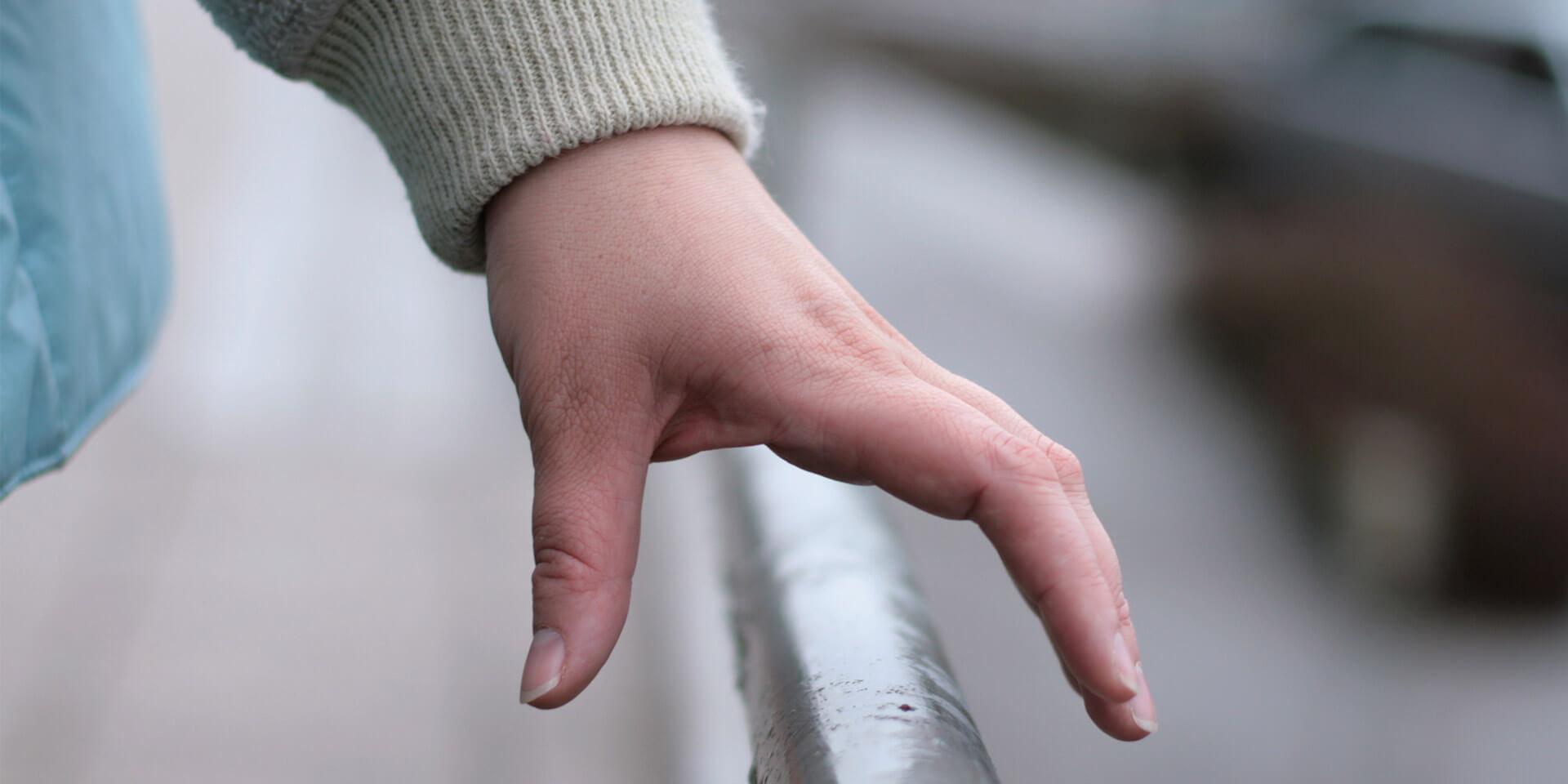 Das Bild zeigt eine Hand an einem Geländer